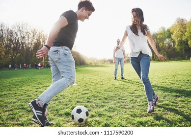 A group of friends in casual outfit play soccer in the open air. People have fun and have fun. Active rest and scenic sunset.