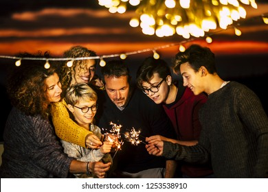 Group of friends celebrate together christmas night or new year eve or birthday or party like anniversary using sparkles light and having a lot of fun in friendship - mixed generations family concept