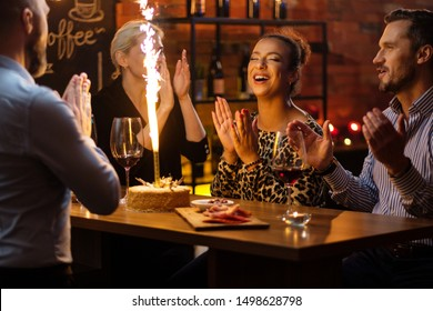 Group of friends celebrating birthday in a cafe behind bar counter