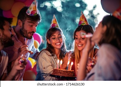 Group of friends celebrating birthday together outdoors.Concept of celebrating and happiness.