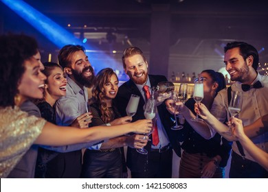 Group of friends celebrating with champagne at the nightclub