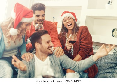 Group of friends celebrating Christmas at home, they are having fun.