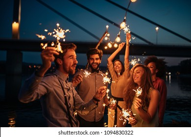 Group of friends celebrating holding sparklers