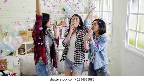 group of friends celebrating and playing with blower whistles at a house party. Young asian women having fun at a colorful home with decorations and confetti all around. carefree girls raising hands.
