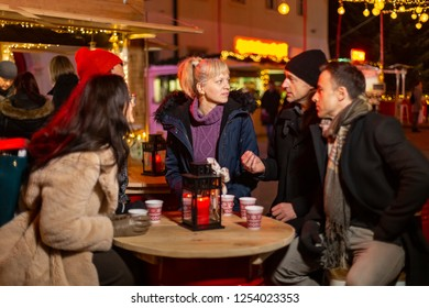 Group of friends chating at Christmas market, Zagreb, Croatia.