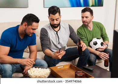 Group of friends checking their team stats on a smartphone while watching a soccer game on TV