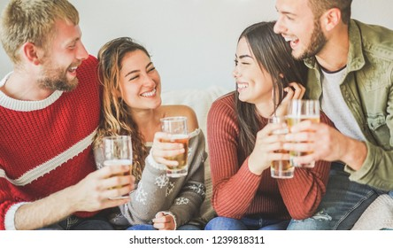 Group of friends cheering with beer at home party - Young people having fun drinking and laughig together - Holiday, youth lifestyle, friendship concept - Focus on left girl