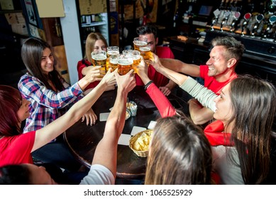 Group of friends cheering on their footbal team at pub - Group of football fans meeting and having party in a bar