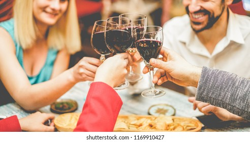 Group of friends cheering with red wine in vintage bar - Young millennials people toasting appetizer in trendy restaurant - Youth lifestyle, nightlife and friendship concept - Focus on right hand