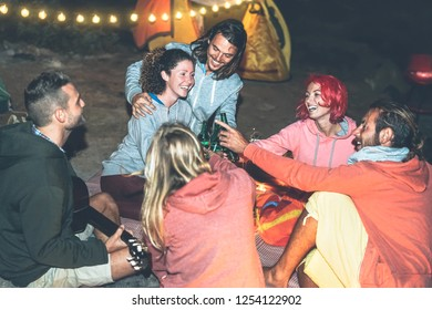 Group of friends cheering and toasting with beer while camping with tent next the beach - Happy young people having fun drinking in campsite with vintage lights - Travel and youth holidays concept