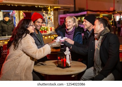 Group of friends cheering with traditional drink at Christmas market, Zagreb, Croatia.