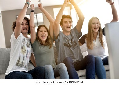 Group of friends cheering up as watching game on TV