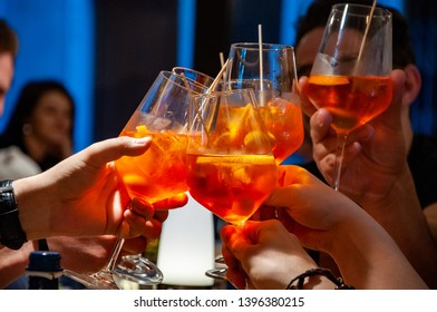 Group of friends cheers with aperol spritz in restaurant. Italian wine-based cocktail.