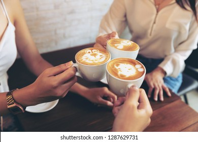 Group of friends cheers with latae cup in cafe bar with phone on table sitting intdoor at cafe - Young girl group having fun drinking together.