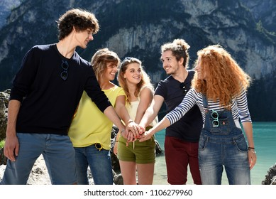 Group of friends with colored shirts hug each other and putting their hands together on the river of an alpine lake in spring or summer time.