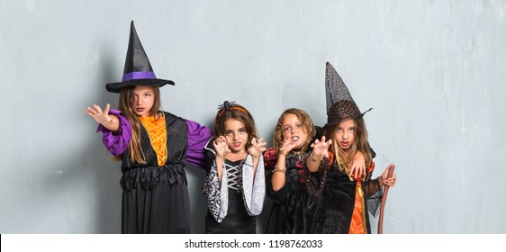 Group of friends with costumes of vampires and witches for halloween holidays making a joke