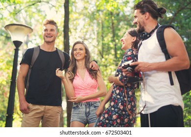 Group of friends or couples having fun with photo camera in summer park