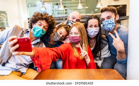 Group of friends covered by face masks taking a selfie with smart phone mobile indoor - New normal friendship concept with young people having fun together at restaurant