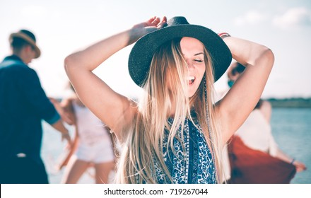 Group of friends dancing and celebrating on beach, boho party outdoor