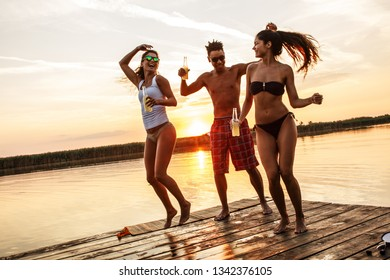 Group of friends dancing and having fun on the pier by the lake on sunset.