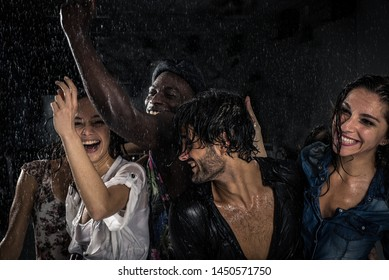 Group of friends dancing in the rain. multiethnic group of people having fun in the summer rain getting wet