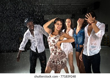 Group of friends dancing under the rain - Multiethnic people having party