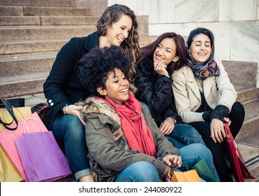 group of friends of different ethnicity sitting on the stairs and having fun