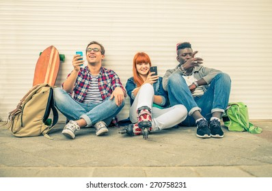 Group of friends of different ethnics sitting on the street and looking at phone - Young hipster people having fun with new technologies - Multiracial group representing the addiction to technology