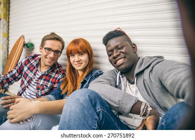 Group of friends of different ethnics taking a selfie - Young modern hipster people having fun and laughing - Multiracial group photographing themselves and looking into camera