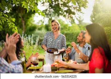 Group of friends dinning on the terrace one summer evening, a beautiful blonde woman brings the cake to table. Shot with flare