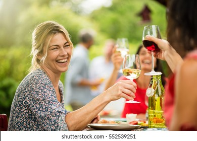 Group of friends doing a bbq, focus on a beautiful woman toasting with her glass of wine. A beautiful garden in the background. Shot with flare