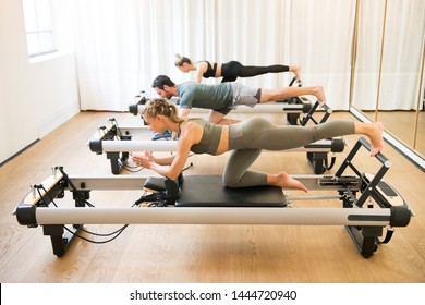 Group of friends doing pilates kneeling glutes exercises on reformer beds in a gym in a health and fitness concept