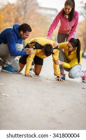 Group of friends doing push-ups at the park and making fun,smiling and laughing.Autumn season.