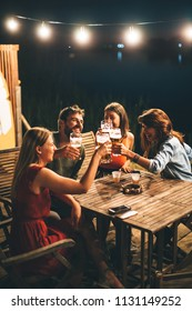 Group of friends drink beer on the terrace and toast during summer night