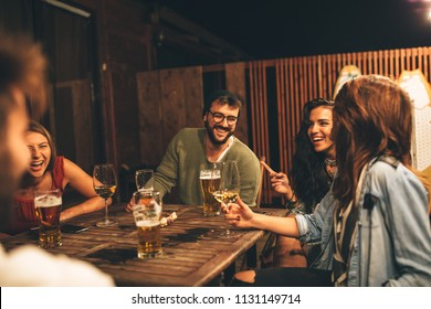 Group of friends drink beer on the terrace during summer night