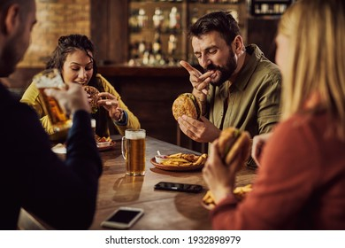 Group of friends drinking beer and eating hamburgers in a pub. Focus is on man tasting a burger.