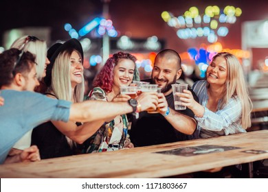 Group of friends drinking beer at music festival