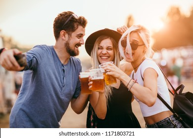 Group of friends drinking beer and taking selfie at music festival