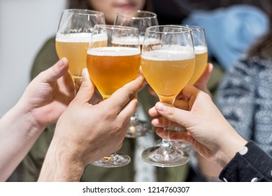 Group of friends drinking beer, toasting, at pub