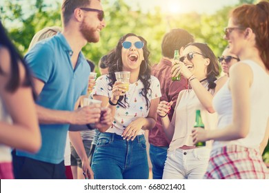 Group of friends drinking, chatting and having a good time at outdoor party