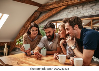A group of friends drinking coffee at the apartment and looking at something on a cellphone.