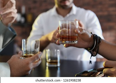 Group of friends drinking whiskey together in bar, closeup