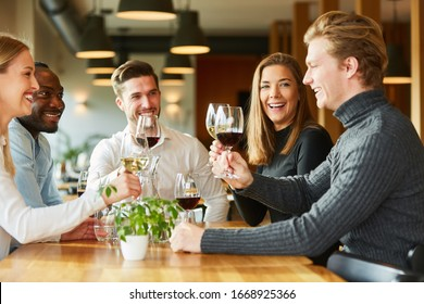 Group of friends drinking wine and toasting in restaurant or bar