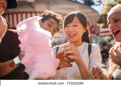 Group of friends eating candyfloss at amusement park. Smiling young people sharing cotton candy outdoors.