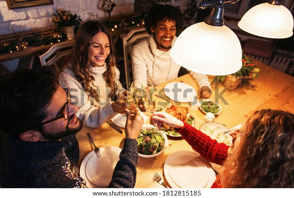 Group of friends eating dinner together, cheering with champagne