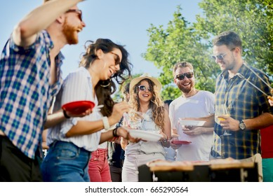 Group of friends eating, drinking, dancing and having a good time at outdoor party