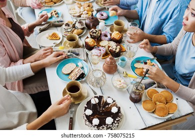 Group of friends eating homemade desserts by festive table