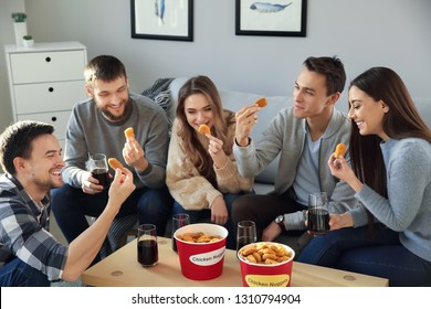 Group of friends eating nuggets at home