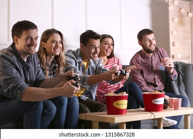 Group of friends eating nuggets while playing video game at home
