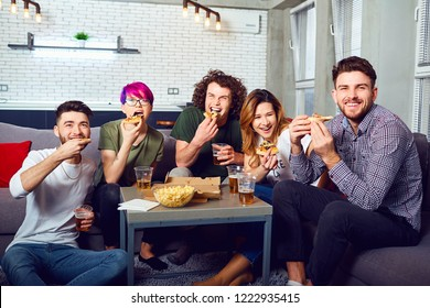 A group of friends eating pizza wathing tv sitting on the couch.